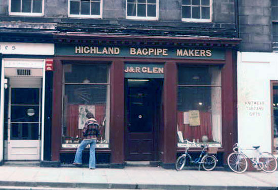 Man standing in front of J&R Glen Highland Bagpipe Makers shop, 1970s